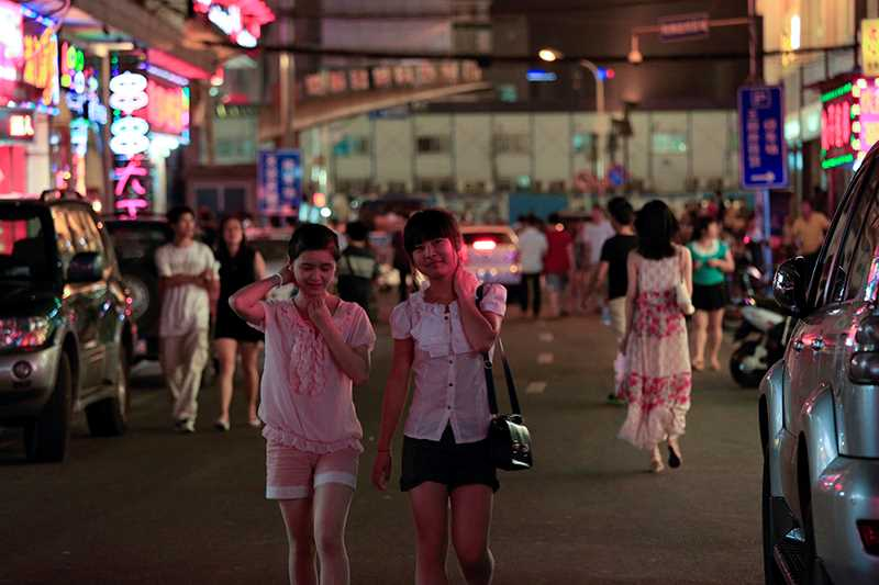 Two young Asian woman walking along a busy street.