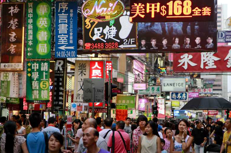 Street with a lot of people walking and neon signs