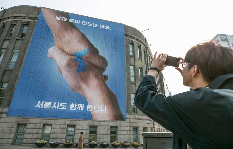 Poster showing a handshake and Korean peninsula