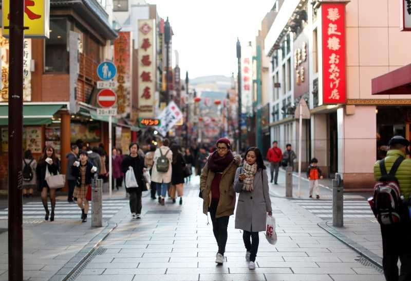 A shopping street in Japan with pedestrians pictured