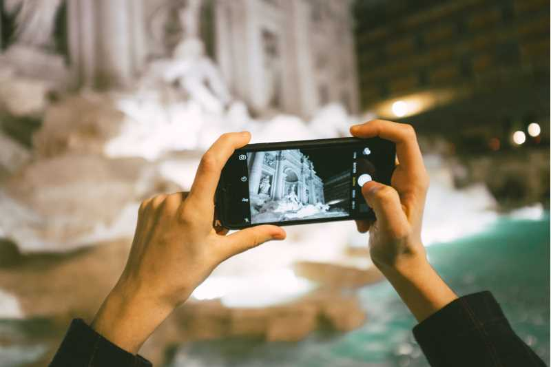 Photo: Two hands holding a mobile and photographing Fontana di Trevi in Rome.