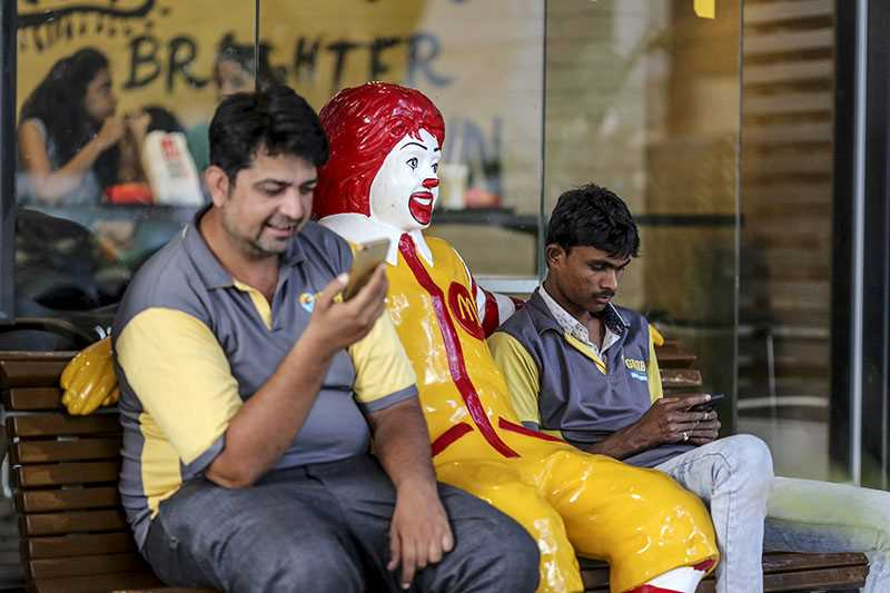 Two men on a bench with statue of Ronald McDonald
